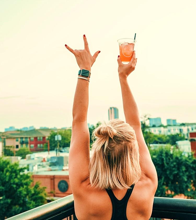 Mujer con bebida en el atardecer